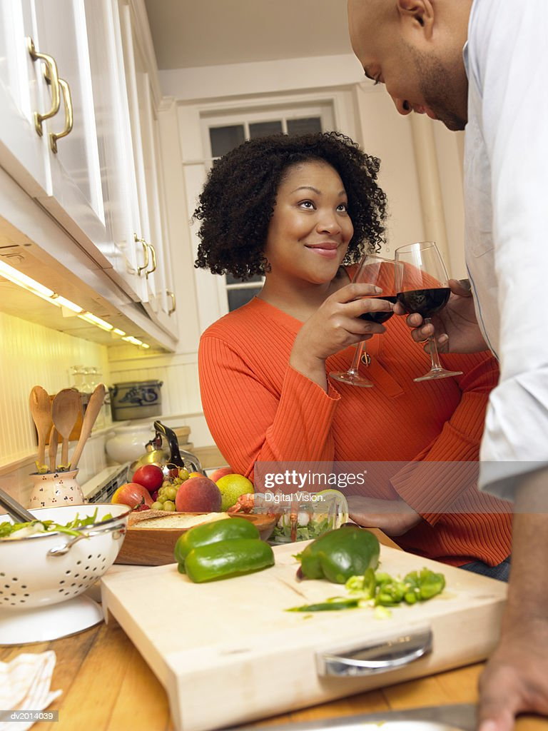 Couple Making a Toast of Red Wine Cooking by Their Kitchen Counter : Stock Photo