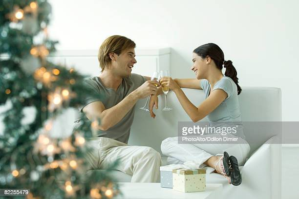 couple making a toast with champagne, christmas tree in foreground - brindis navidad fotografías e imágenes de stock