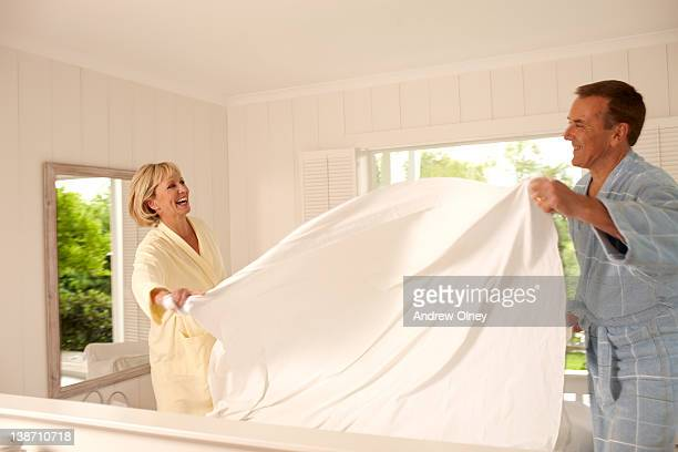 Couple making bed together in the morning