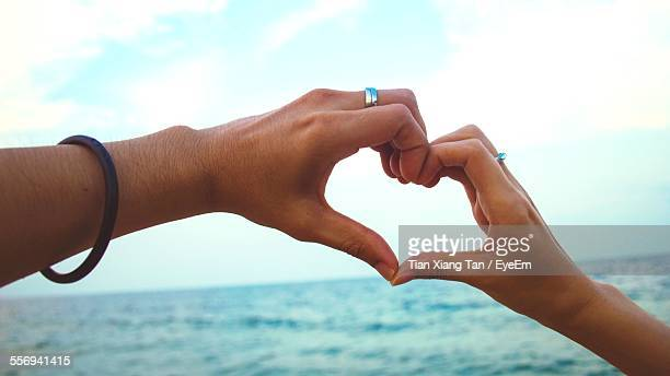 Couple Making Heart Shape With Hands On Beach