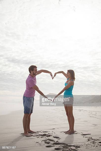 couple making heart together on beach - gesturing stock pictures, royalty-free photos & images
