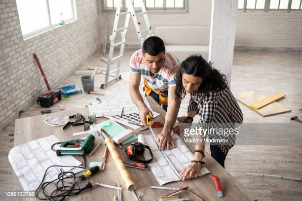 couple making home improvement and measuring - mid adult women stock pictures, royalty-free photos & images
