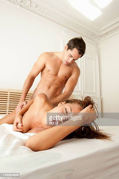 couple making love in bed - erotiek stockfoto's en -beelden