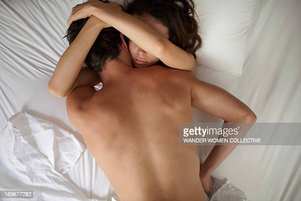 Couple making love in bed with white sheets