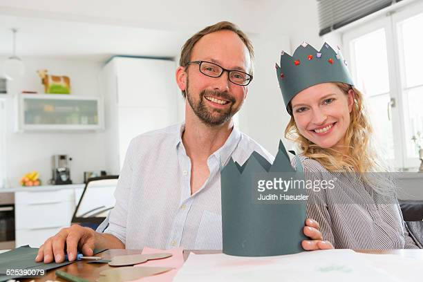 Couple making paper crowns
