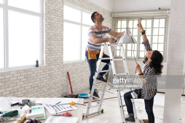 couple making renovations, changing lighting equipment - home improvement stock pictures, royalty-free photos & images