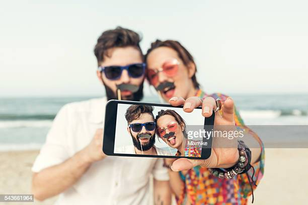 Couple making selfie on the beach with fake moustaches