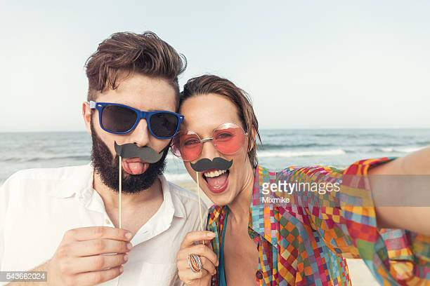 couple making selfie on the beach with fake moustaches - freaky couples stock photos and pictures