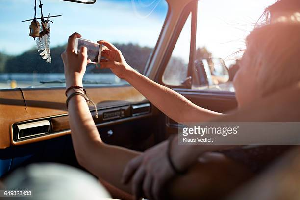 Couple making selfie with phone, while riding car