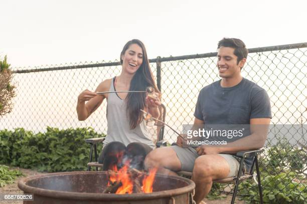 Couple Making Smores By The Campfire At Sunset