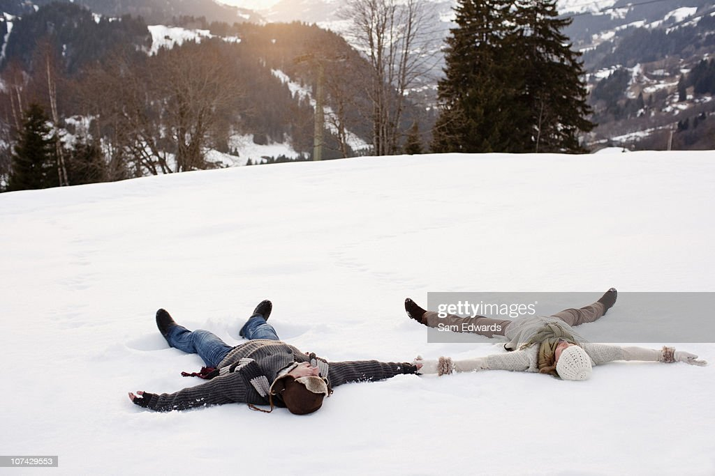 Couple making snow angels : Stock Photo