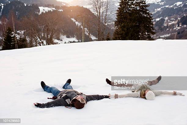 couple making snow angels - snow angel stock photos and pictures