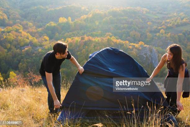Couple making tent on the hill