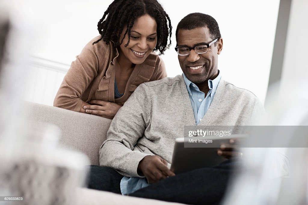 A couple, man and woman seated sharing a digital tablet.  : Stock Photo