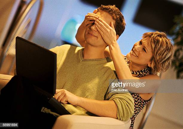 Couple, man using laptop, woman covering man's eyes from behind