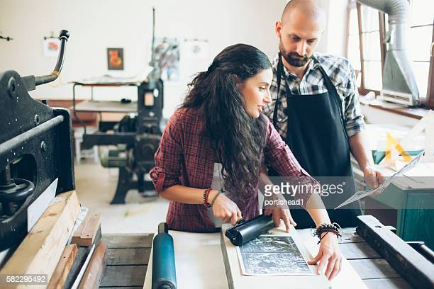 Couple manual workers at printing house
