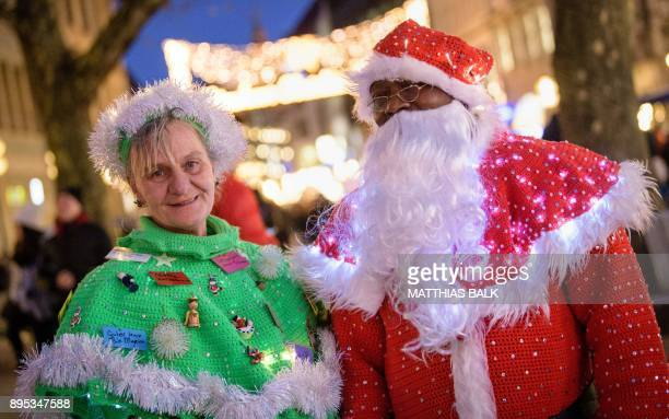 Couple Manuela and Jules Samlan pose in their selfmade Christmas Tree and Santa Claus costumes as they walk along a shopping street in Munich...