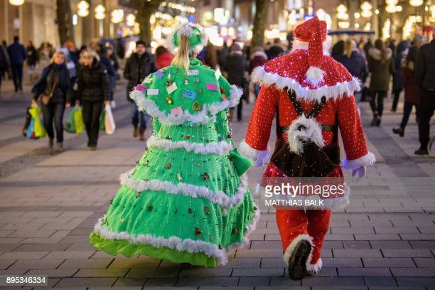 Couple Manuela and Jules Samlan wear their selfmade Christmas Tree and Santa Claus costumes as they walk along a shopping street in Munich southern...