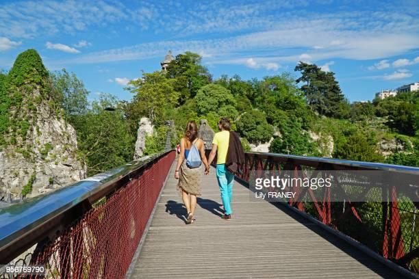 Couple marchant sur le pont suspendu dans le parc des Buttes Chaumont au printemps 24 avril 2017 Paris 19ème France
