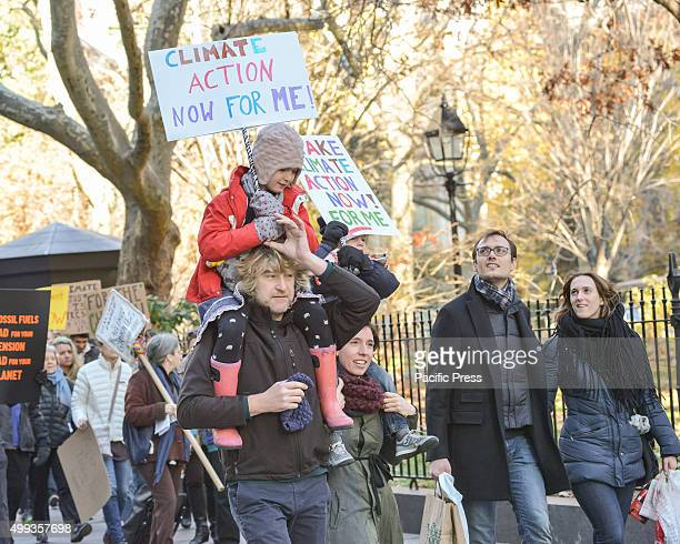 A couple marching in the NYC Global Climate March carry their children who in turn carry signs on their shoulders On the eve of the Paris Climate...