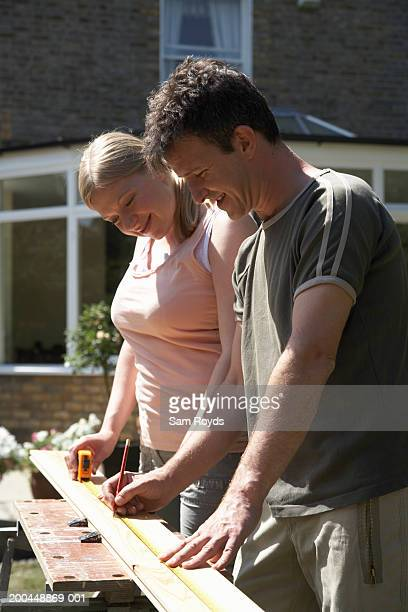 Couple measuring and marking piece of timber in garden, smiling