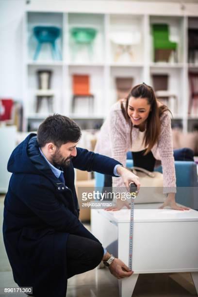 Couple measuring  in furniture shop