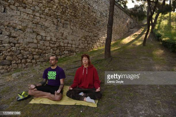 Couple meditate on De la Vega Slope on May 07, 2020 in Madrid, Spain. The Spanish government is allowing restricted opening of businesses such as...