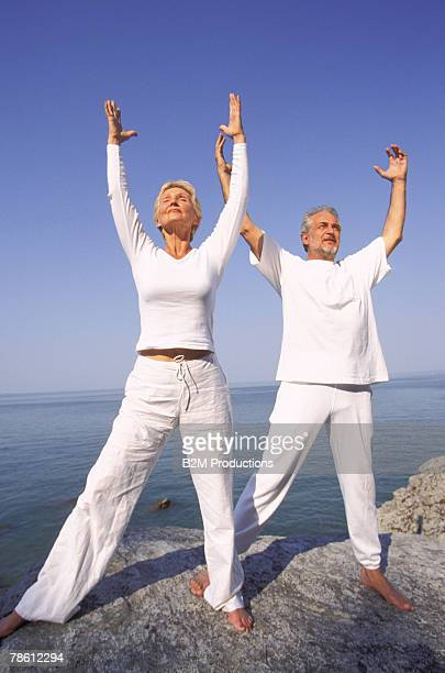 couple meditating near ocean - heterosexual couple stock pictures, royalty-free photos & images