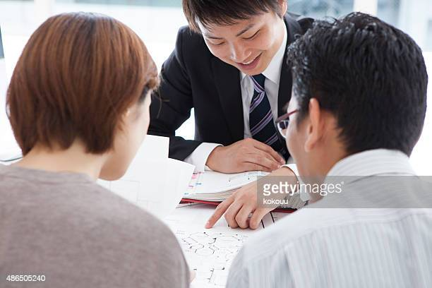 couple meeting architect for plans of future home - real estate office stock photos and pictures