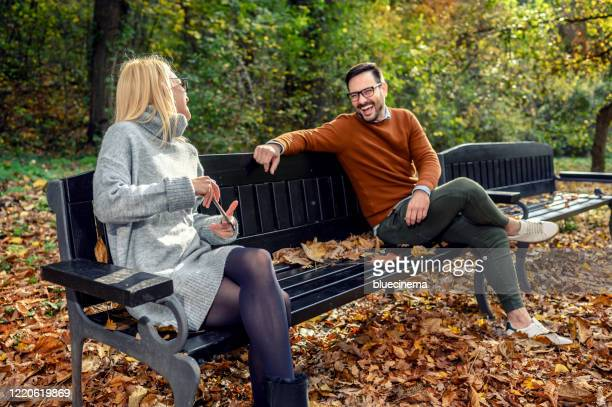 couple meeting outside - park bench stock pictures, royalty-free photos & images