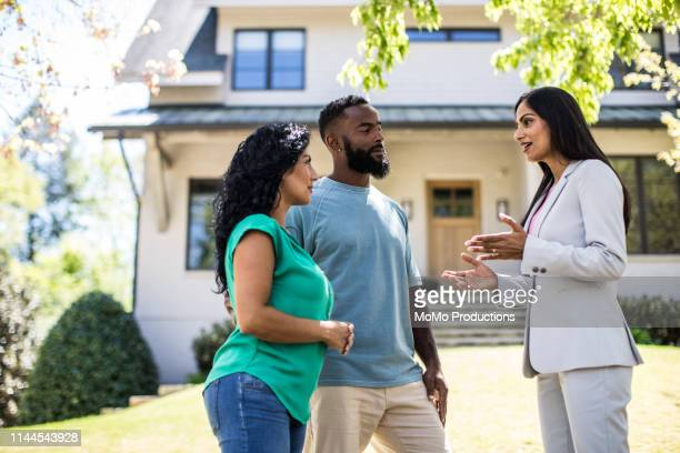 couple meeting with real estate agent in front of home - real estate stock pictures, royalty-free photos & images