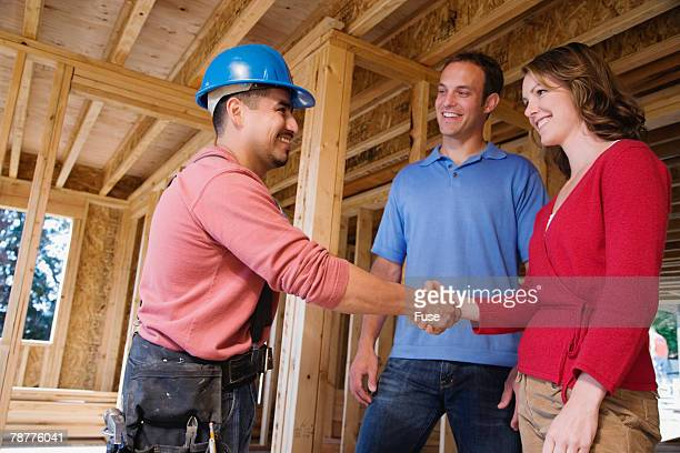 Couple Meeting Worker in their Home under Construction