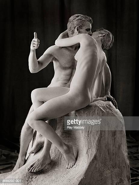 Couple mimicking Rodin's 'The Kiss' with man raising thumb (toned B&W)