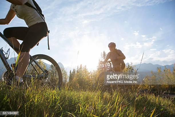 couple mountain bike along grassy ridge crest - mountain ridge stock pictures, royalty-free photos & images