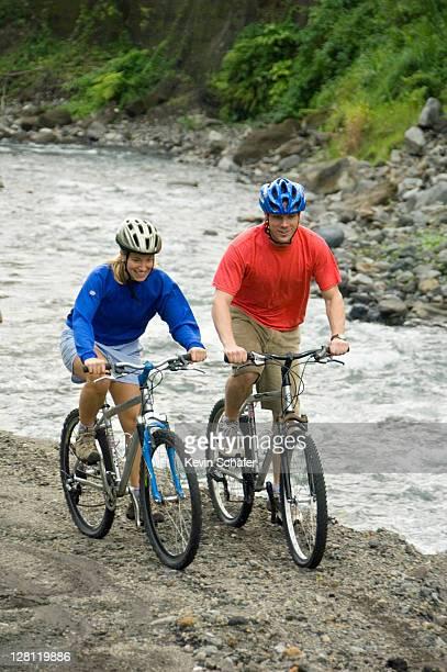 Couple Mountain biking. Arenal, Costa Rica (MR)