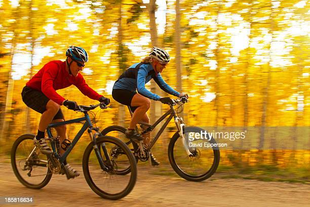 couple mountain biking in fall, speed blur - steamboat springs colorado stock photos and pictures
