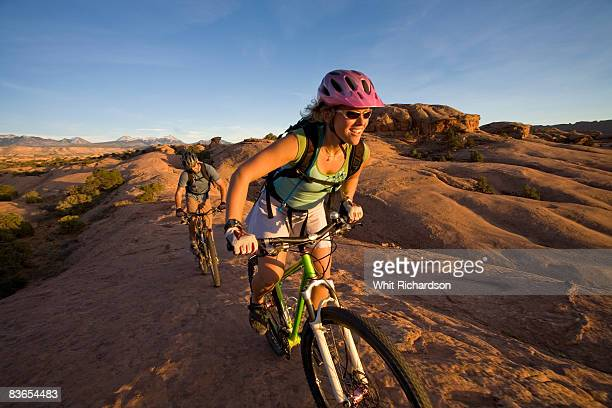 couple mountain biking, moab, utah - moab utah stock photos and pictures
