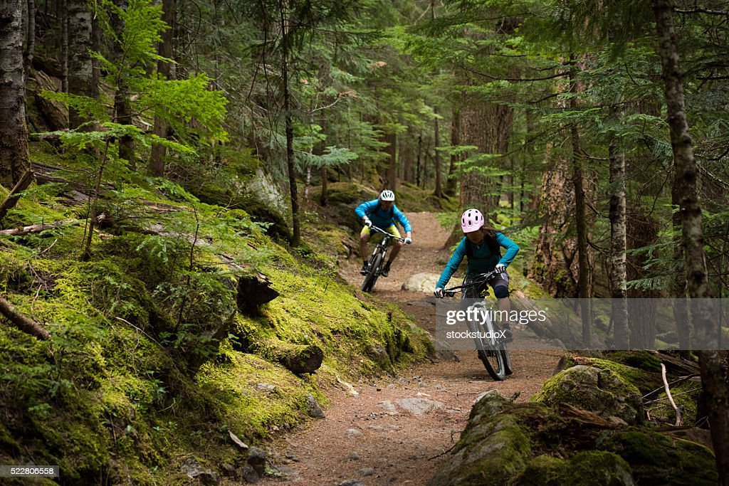 Couple mountain biking through a forest : Stock Photo