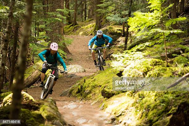 Couple mountain biking through a forest