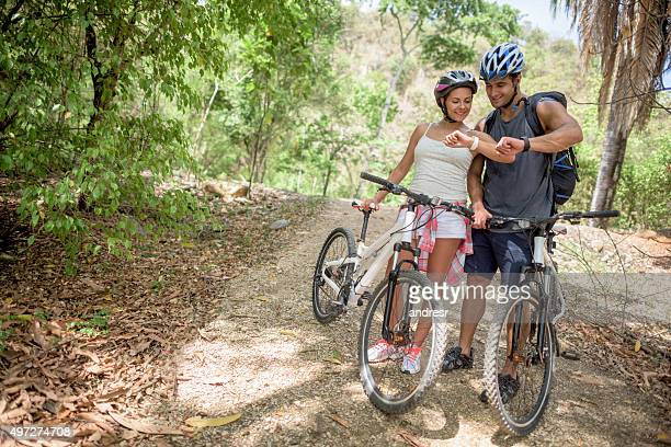 Couple mountain biking using a smart watch