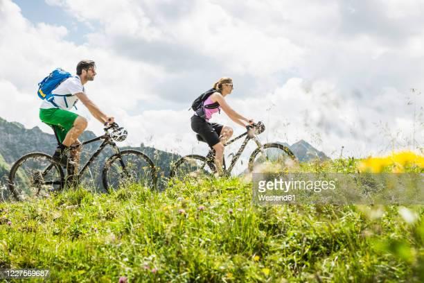 couple mountainbiking in the mountains, achenkirch, austria - austria stock pictures, royalty-free photos & images