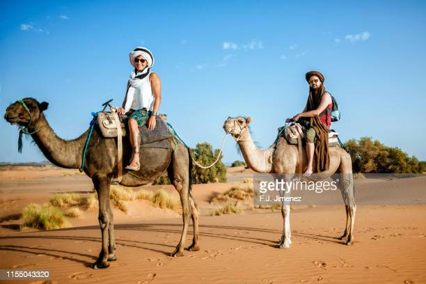 couple mounted a camel in the desert - traditional clothing stock pictures, royalty-free photos & images