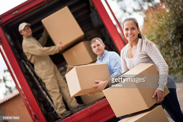 Couple moving and movers loading the van