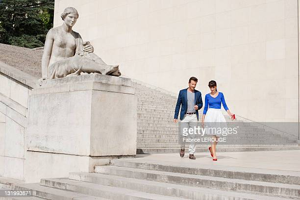 Couple moving down steps, Paris, Ile-de-France, France