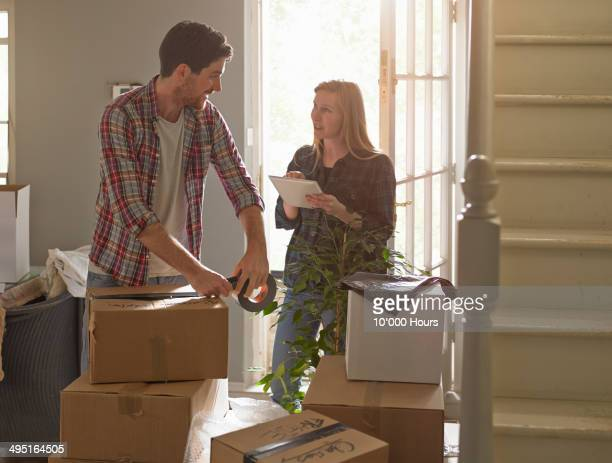 a couple moving home, the woman is using an tablet computer - 引っ越し ストックフォトと画像