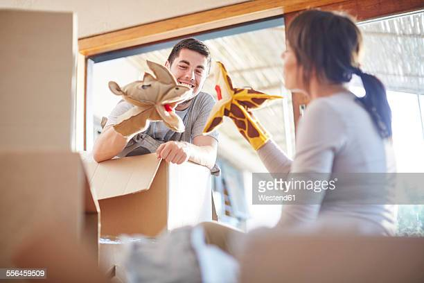 Couple moving house playing with animal hand puppets