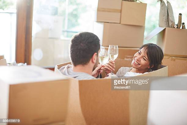 Couple moving house sitting in a box and clinking wine glasses