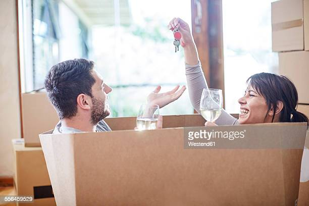 Couple moving house sitting in a box with key and wine glasses