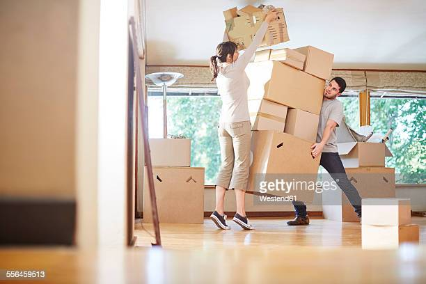 Couple moving house stacking boxes