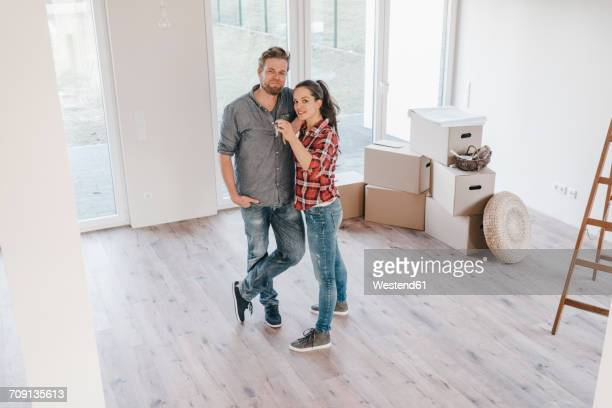 Couple moving house, woman holding keys of new home
